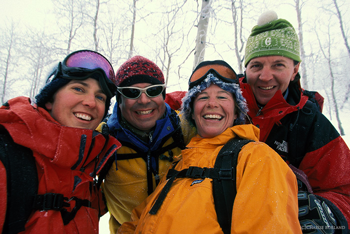 four hikers smiling at the camera on an adventure photography trip, the snow and bare trees behind them
