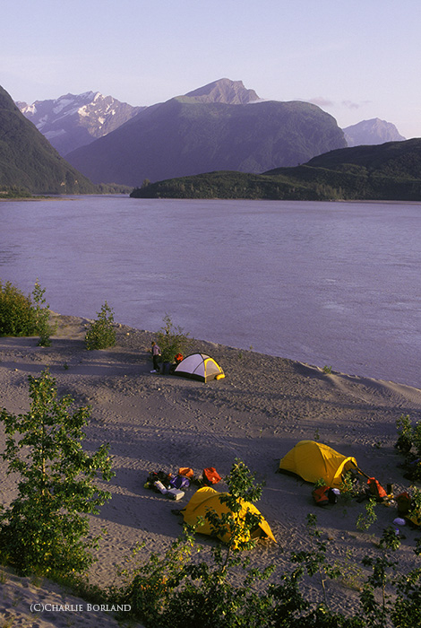 view of camping tents by a lake with mountains in the horizon
