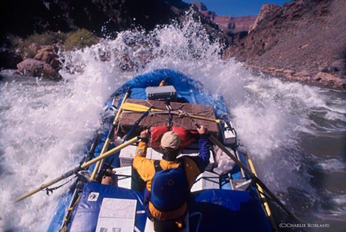 man in a blue raft rowing down the rough river rapids, rocks on either side