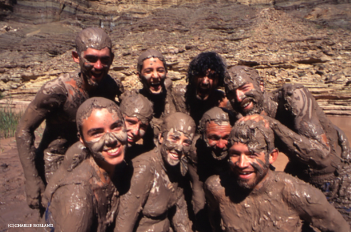 hiker adventurers covered in mud smiling in to the camera, the rocky mountain side behind them