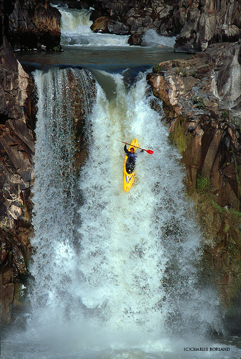 man rowing the rapids in a yellow canoe going down a waterfall
