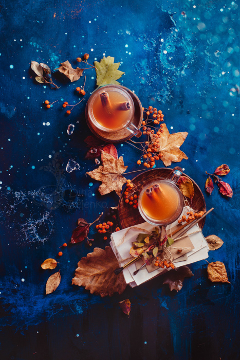 Autumn hot tea with ginger and cinnamon in a glass tea cup on a wet wooden background with copy space. Rainy autumn concept with fallen leaves and letters