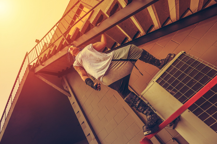 Atmospheric photo of a man posing on a railing and door frame, shot from a low angle