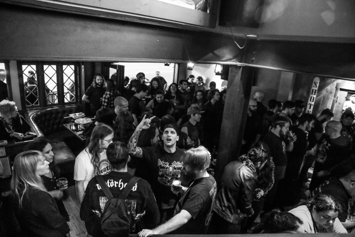 A black and white event photography shot of a crowd in the interior of a bar or concert venue