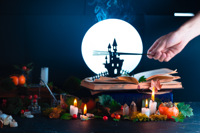 A still life featuring spooky halloween castle silhouette, a full moon and other photography props
