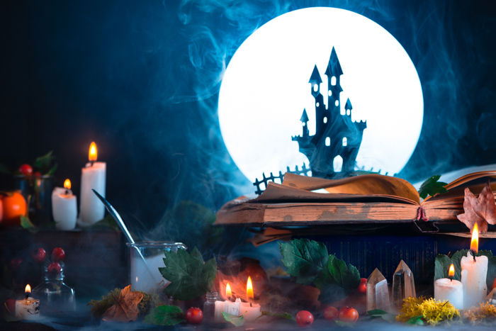 A still life featuring a spooky castle silhouette, a full moon, candles and other spooky props - cool halloween photos