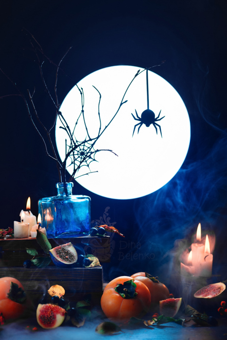 A scary still life featuring the silhouette of a spider, a full moon, candles and other spooky props