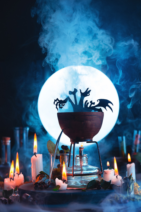 Atmospheric Halloween still life featuring a a cauldron, a full moon, candles and other spooky props