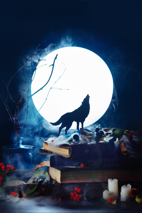 Atmospheric Halloween still life featuring the silhouette of a wolf howling in front of a full moon