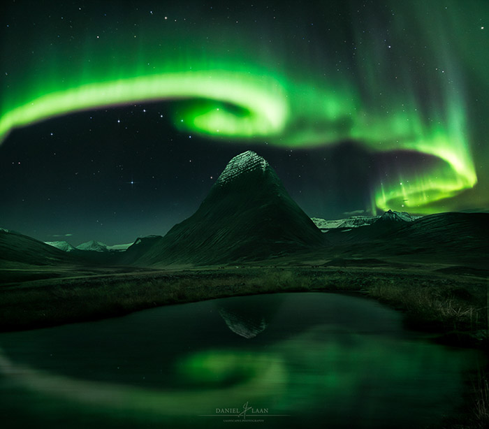 Stunning shot of the northern lights swirling over a mountainous landscape