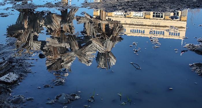 Uma foto impressionante de arte e arquitetura refletida em uma poça, aperfeiçoada usando a ferramenta de correção do Photoshop