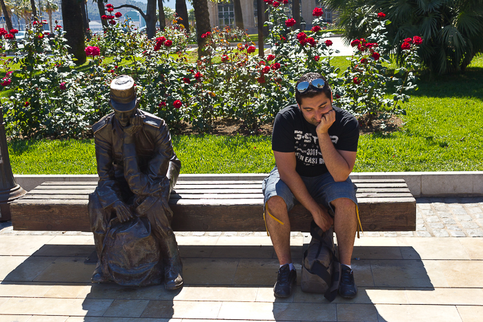 A man sitting beside a statue on a bench