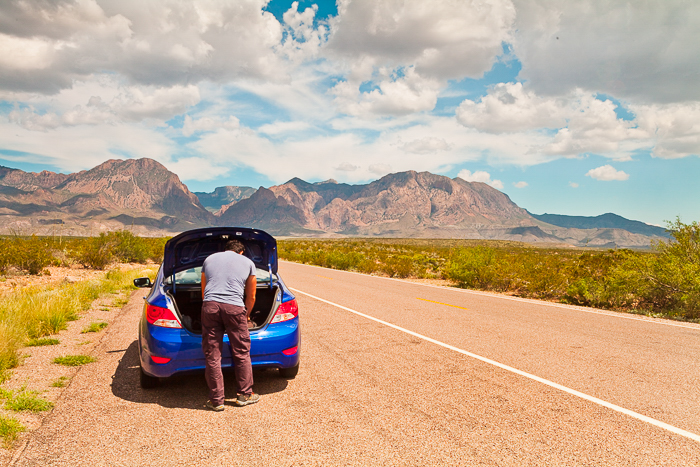 Man looking into the trunk of his blue car, stopped at the side of a pale brown road leading to the mountains in the distance