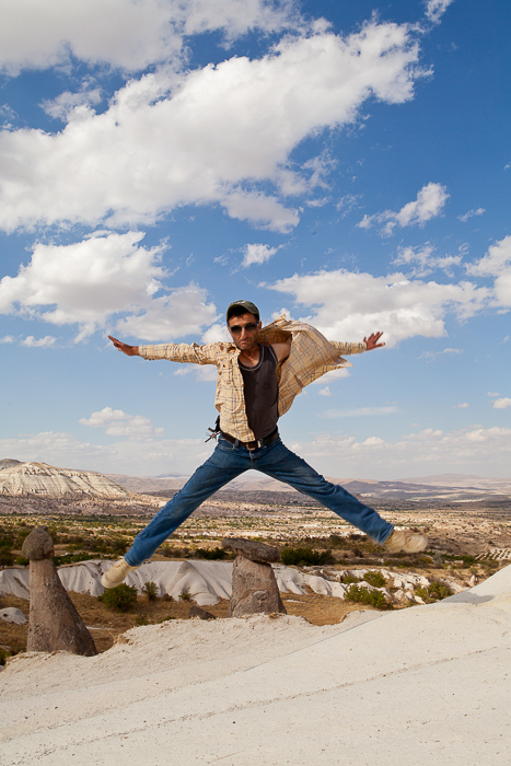 jumpshot of a man in jeans and sunglasses, on a dust road overlooking rocky cliffs on a bright sunny afternoon