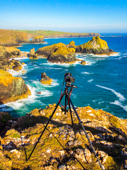 DSLR set up on a tripod at the top of brown rocks overlooking a rocky shore to a deep blue sea