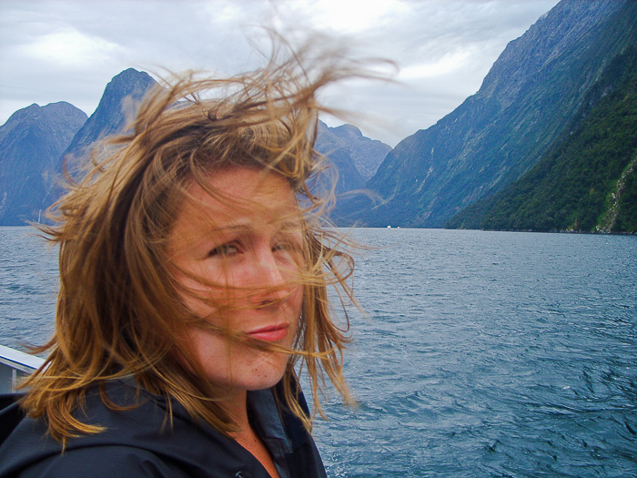 A woman taking a selfie in front of a blue lake, sky and mountains, the wind blowing her short blonde hair in her face