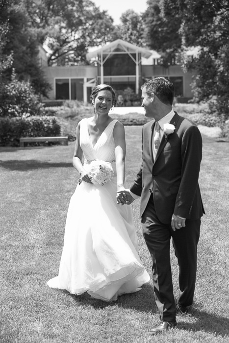 black and white photo of newly weds bride and groom holding hands, laughing, walking across a lawn