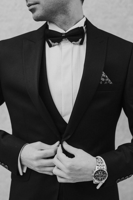 A black and white portrait of a man buttoning his tuxedo jacket