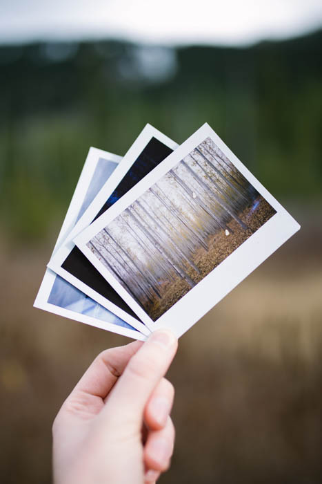 A hand hold three printed photos