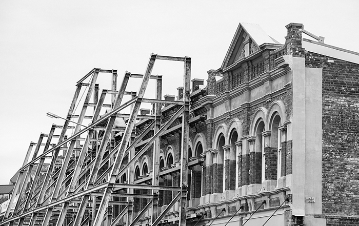 black and white photo of an old building of old architecture, scaffolding leaning up against its face - black and white photo editing
