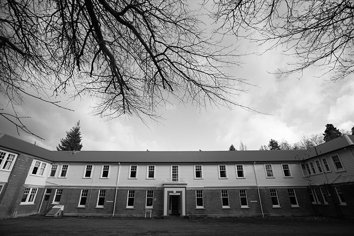 black and whit photo of the front of the Queen Mary Hospital Nurse's Hostel, bare branches on a nearby tree