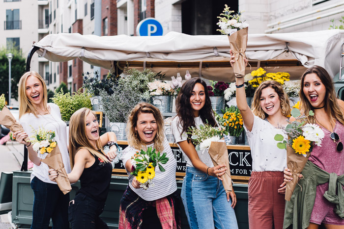 Fun group photo of girls holding bunches of flowers and smiling