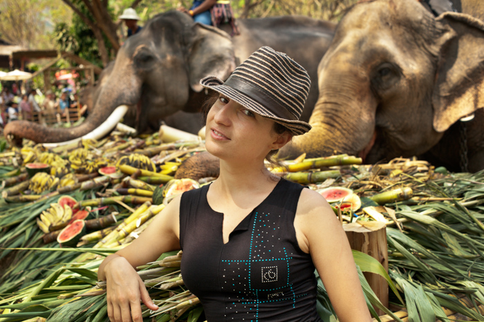 European woman tourist enjoys being with elepants on National Elephant Day in Thailand