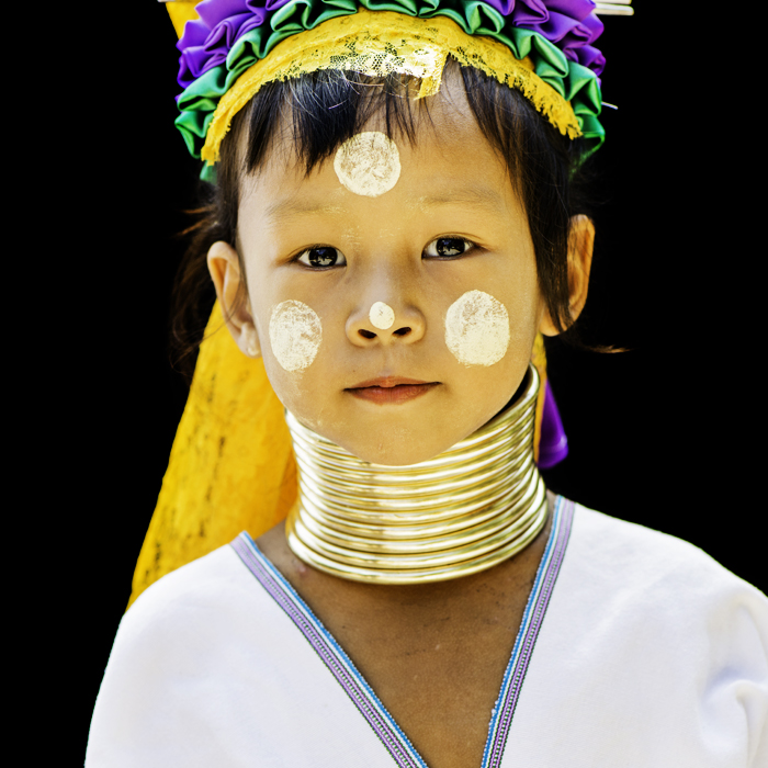 A portrait of a young thai girl in traditional costume using central composition on black background