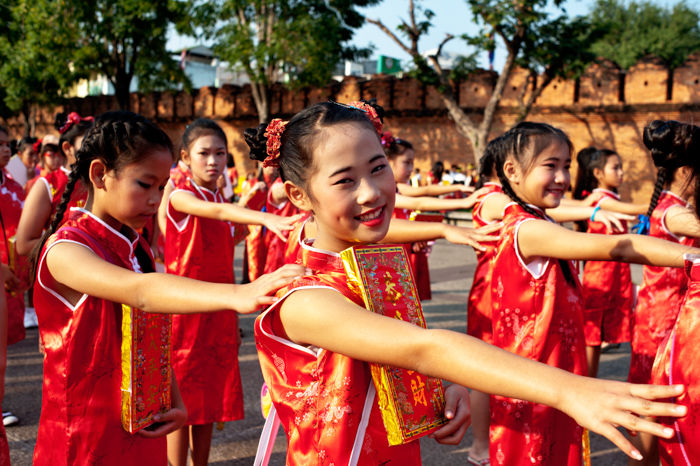 Asian girls wearing traditional red dresses line up for the Chinese new year parade in Chiang Mai, Thailand.