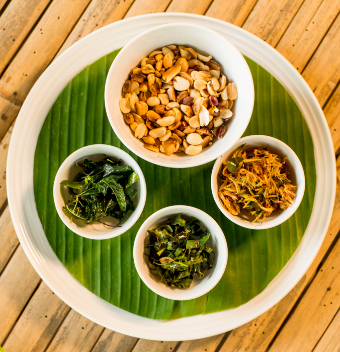 A centrally placed round plate with four round bowls and the green banana leaf