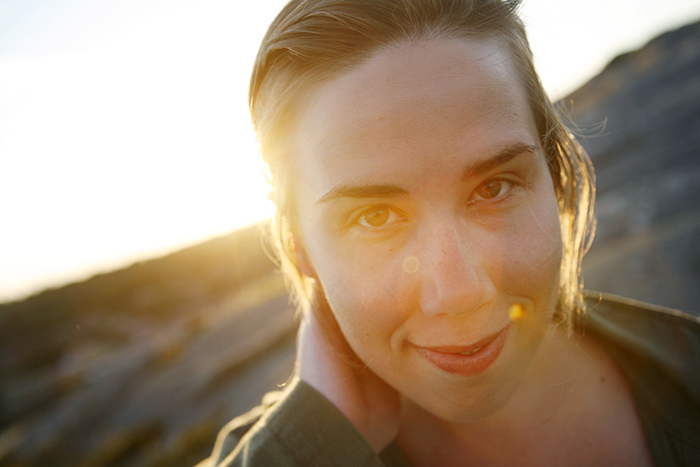Close-up portrait of smiling woman during sunset.