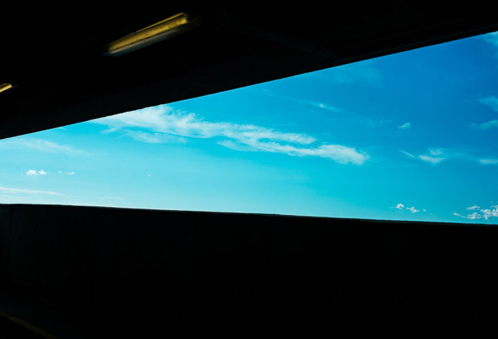 A turquoise blue sky with small clouds shot using a ND filter
