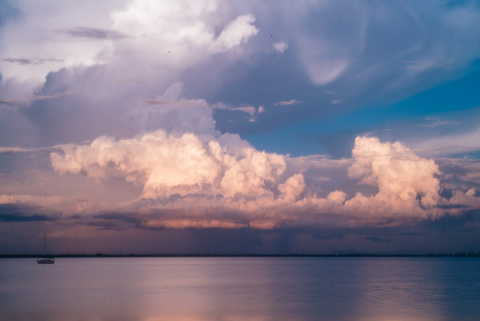 A pretty coastal seascape shot at evening time with large fluffy clouds above