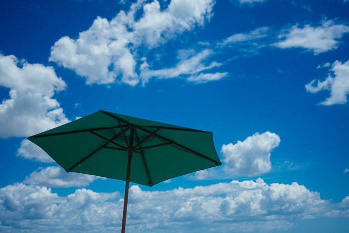 A green umbrella against blue skies with fluffy clouds