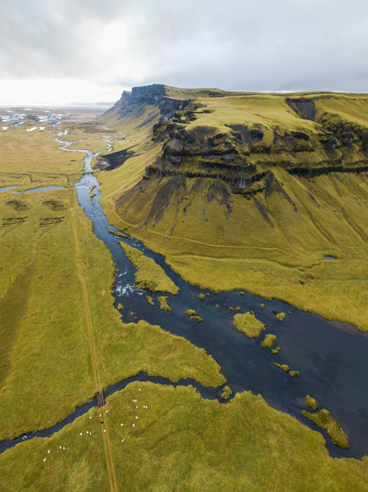 A stunning aerial shot of a green landscape, with river and mountain, shot on an overcast cloudy day