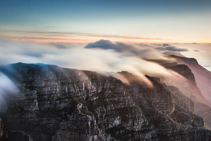 Atmospheric landscape shot of rocky cliff stops covered in mist and fog, cloudy day photography