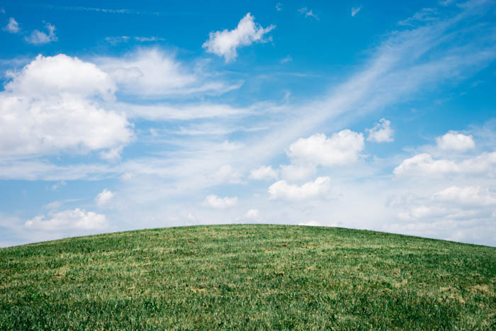 serene outdoor photo, green glass hill on a cloudy day