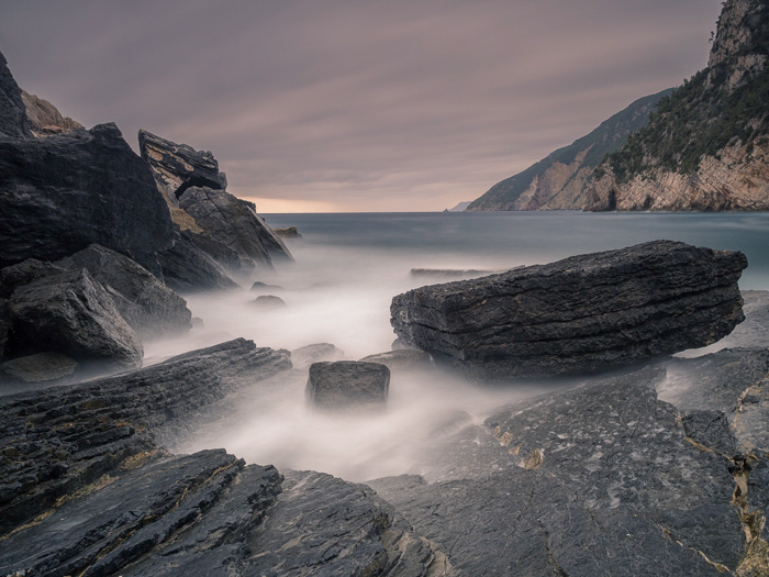 long exposure photo of the Rocks and the waves on the Porto Venere coast at sunrise.