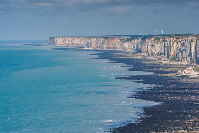 High point of view photo of a cliff side in the horizon against a blue sea and clear blue sky