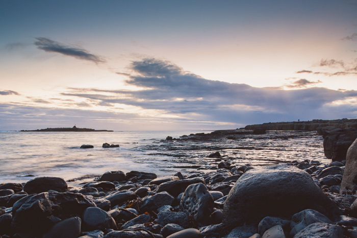 Low vantage point photo of rocks at the coast at sunrise against a cloudy soft lit sunrise