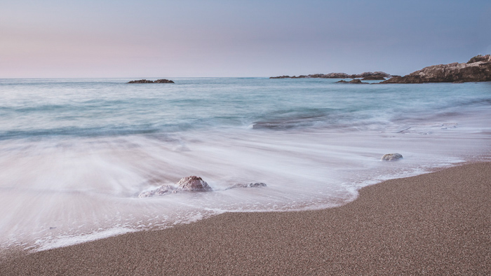 Photo of soft foamy waves on pinkish sand from a crystal blue sea against a pastel sunrise