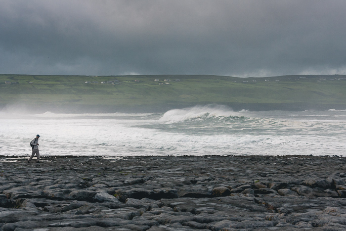 A lone silhouette of a man walking along a beach with big waves behind him.