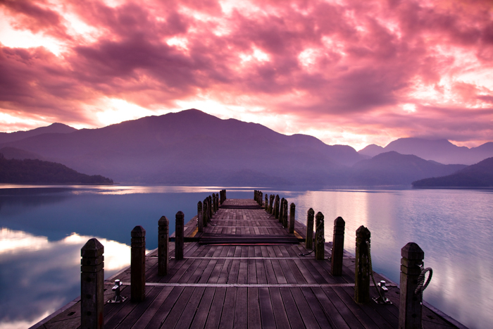 A wooden pier on a lake during a beautiful sunset