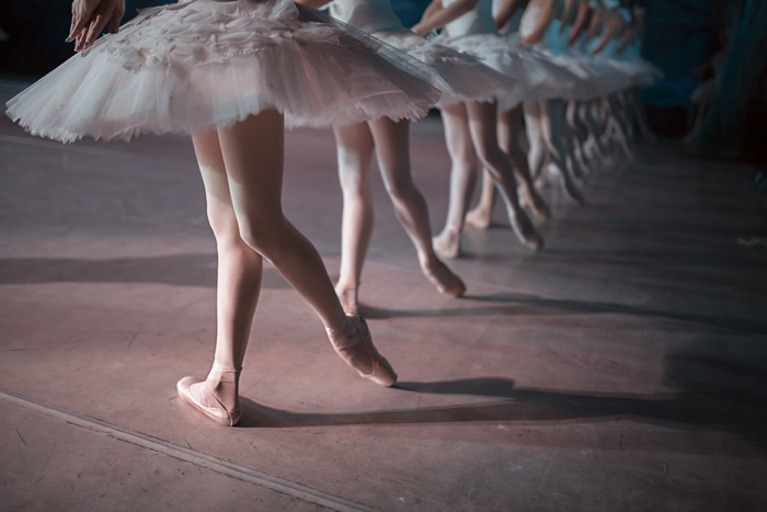 The legs of a row of dancers in white tutu synchronized dancing on stage
