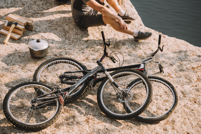 Cropped photo composition of a man sitting on rocks beside two bicycles