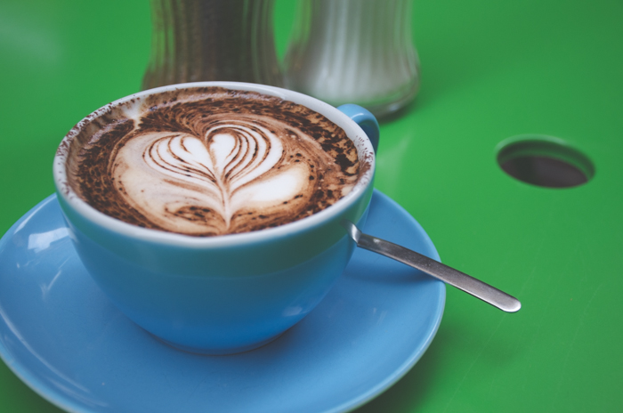 Close up photo of a cappuccino in a blue coffee cup on green background demonstrating color contrast images