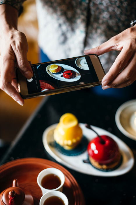 A close up of a person taking a food photography shot with a smartphone