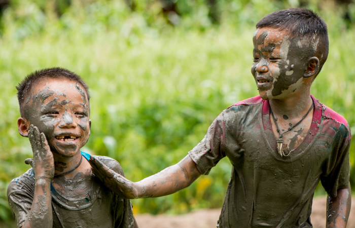 Two laughing Thai boys covered in mud - figure photography