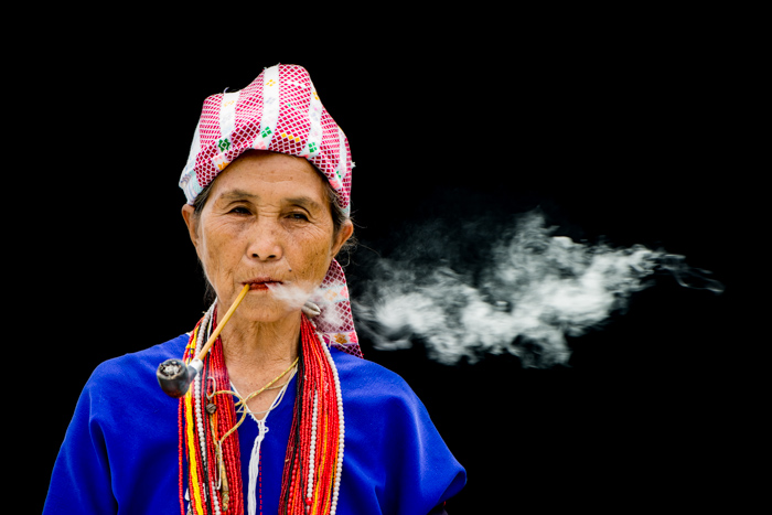 A Karen Woman Smoking a pipe against a black background - figure to ground photography composition