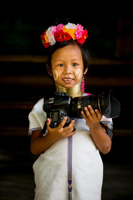 A young karen girl holding a large DSLR camera
